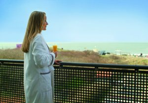 Strandhotel Nehalennia VisitDomburg - foto van vrouw op balkon bij hotelkamer